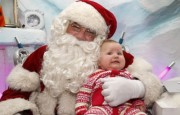 Actor Warren, who has been playing Santa for the past ten years, holds seven-month-old Olivia Ruch at Santa's Grotto in Selfridges department store in London